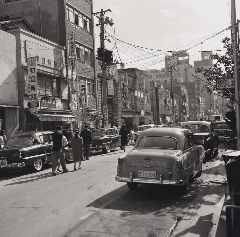 1950s, historical picture of a street in the Old Town of Tokyo, Japan, with many larger American style motorcars of the era parked at the side of the road.