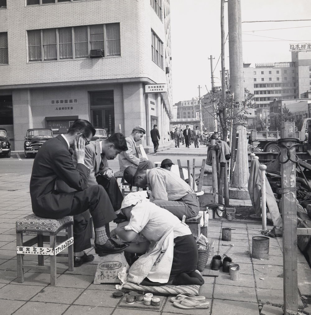 Tokyo, Japan, 1950s, historical picture showing Japanese businessmen having their shoes cleaned and polished by the shoe shine ladies working on the pavement outside.
